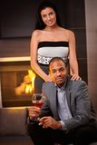 Attractive interracial couple at home by fireplace Royalty Free Stock Photography