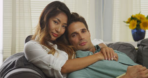 Attractive interracial couple sitting on couch Royalty Free Stock Images