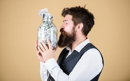 Attractive investment. Bearded man investor kissing glass jar with investment money. Successful businessman making a stock image