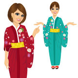 Attractive japanese woman wearing kimono with flowers pointing and holding something Stock Photo