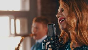 Attractive jazz vocalist with red lips performing on stage with saxophonist. Retro style stock video footage