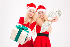 Attractive joyful blonde sisters twins posing with money and present Royalty Free Stock Photography