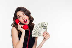 Attractive joyful curly female holding money and talking on telephone Stock Photo