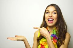 Attractive joyful girl ready for carnival party showing and pointing your product or text on white background. Stock Photography