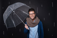 Attractive joyful man holding an umbrella. Royalty Free Stock Image