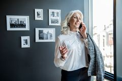 Attractive joyful old lady is communicating using smartphone stock photography