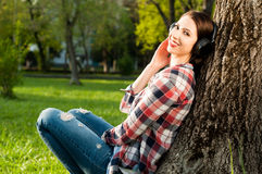 Attractive joyful woman sitting outside under tree and listening Stock Image