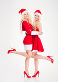 Attractive joyful women in santa claus costumes standing and smiling Royalty Free Stock Image