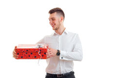 Attractive joyful young man holding a large gift packaging royalty free stock photos