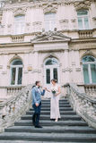 Attractive just married pair going down by ancient stairs near the old austrian palace Stock Photo