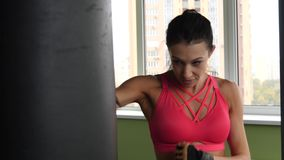 Attractive kickboxing mixed race woman training punching bag in fitness studio fierce strength in slow motion. Fit body boxer stock video