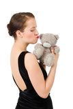Attractive kissing brunette holding teddy bear Royalty Free Stock Photography