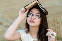 Attractive Korean girl with glasses covers head with book royalty free stock images