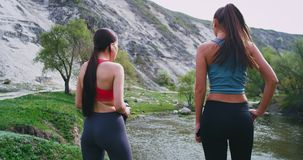Attractive ladies with a fit bodies after a running workout tired stopped for a bit in amazing landscape view to take a