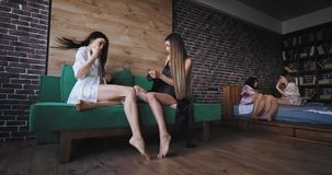 Attractive ladies in the morning have a great mood in pajamas sitting on the sofa and chatting with each other on the stock video