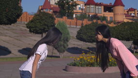 Attractive ladies say hello in sunny day outdoors. Two young asian women meeting on the street greeting with regards. Woman with long black hair wearing in stock video footage