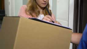 Attractive lady accepting parcel in cardboard box and signing documents delivery