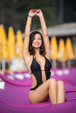 Attractive lady in a black swimsuit sitting on a purple lounger on the luxury resort with blurred background. Attractive brunette lady in a black swimsuit Royalty Free Stock Photo