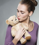 Attractive lady blowing her cuddly toy a kiss Stock Photo