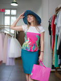 An attractive lady in a blue boar-brimmed hat makes purchases on a clothing shop background. Sale and fashion concept. Stock Photography