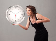 Attractive lady holding a huge clock Royalty Free Stock Images