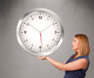 Attractive lady holding a huge clock Royalty Free Stock Image