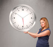 Attractive lady holding a huge clock Stock Photos