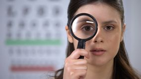 Attractive lady looking through lens and smiling, eye cornea genetics, treatment
