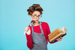 Attractive lady looks for new recipe holding soup ladle in hands Stock Photography