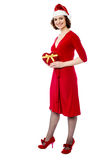 Attractive lady in red attire with xmas gift Royalty Free Stock Photos