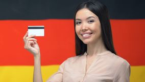 Attractive lady showing credit card on German flag background, financial fund