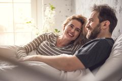 Two loving people are enjoying themselves in bed. Attractive lady is smiling to partner while they are hanging out in dormitory during morning time. Relaxed Stock Photos