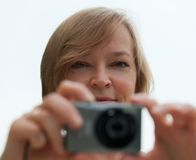 Attractive lady taking photo with digital camera. Stock Images