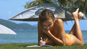 Attractive Lady Writes with Pen on Green Lawn. Attractive long haired young lady writes with blue pen on green lawn against beach umbrellas and palm trees stock footage