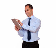 Attractive latin adult man using his tablet pc royalty free stock image