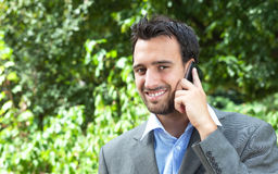 Attractive latin businessman on the phone in a park Royalty Free Stock Image
