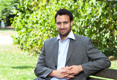 Attractive latin businessman relaxing in a park Royalty Free Stock Photography