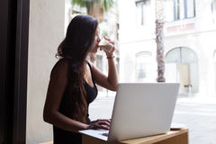 Attractive latin female enjoying her drink while working on net-book in cafe outdoors Stock Images