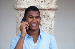 Attractive latin guy with phone in a colonial town Stock Photos
