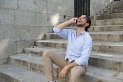 Attractive latin man on city staircase talking happy on mobile phone looking satisfied and confident Stock Photography