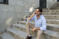 Attractive latin man on city staircase talking happy on mobile phone looking satisfied and confident Royalty Free Stock Image