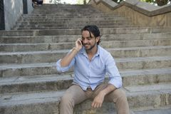 Attractive latin man on city staircase talking happy on mobile phone looking satisfied and confident Royalty Free Stock Photography
