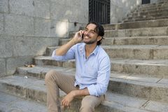 Attractive latin man on city staircase talking happy on mobile phone looking satisfied and confident Stock Photos