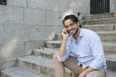 Attractive latin man on city staircase talking happy on mobile phone looking satisfied and confident Royalty Free Stock Photos