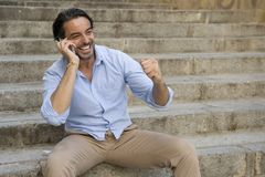 Attractive latin man on city staircase talking happy on mobile phone looking satisfied and confident Stock Image