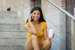 Attractive latin woman in her twenties happy talking her mobile smart phone. While drinking a coffee sitting on stairs Royalty Free Stock Photos