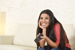 Attractive latin woman at home sofa couch laughing and smiling happy watching television. Young beautiful and attractive latin woman at home sofa couch laughing Stock Photography