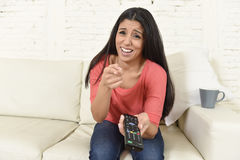 Attractive latin woman at home sofa couch laughing and smiling happy watching television. Young beautiful and attractive latin woman at home sofa couch laughing Stock Photos