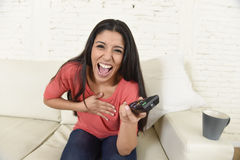 Attractive latin woman at home sofa couch laughing and smiling happy watching television. Young beautiful and attractive latin woman at home sofa couch laughing Royalty Free Stock Images