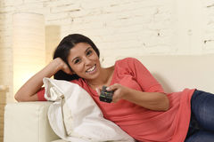 Attractive latin woman at home sofa couch laughing and smiling happy watching television. Young beautiful and attractive latin woman at home sofa couch laughing Stock Images